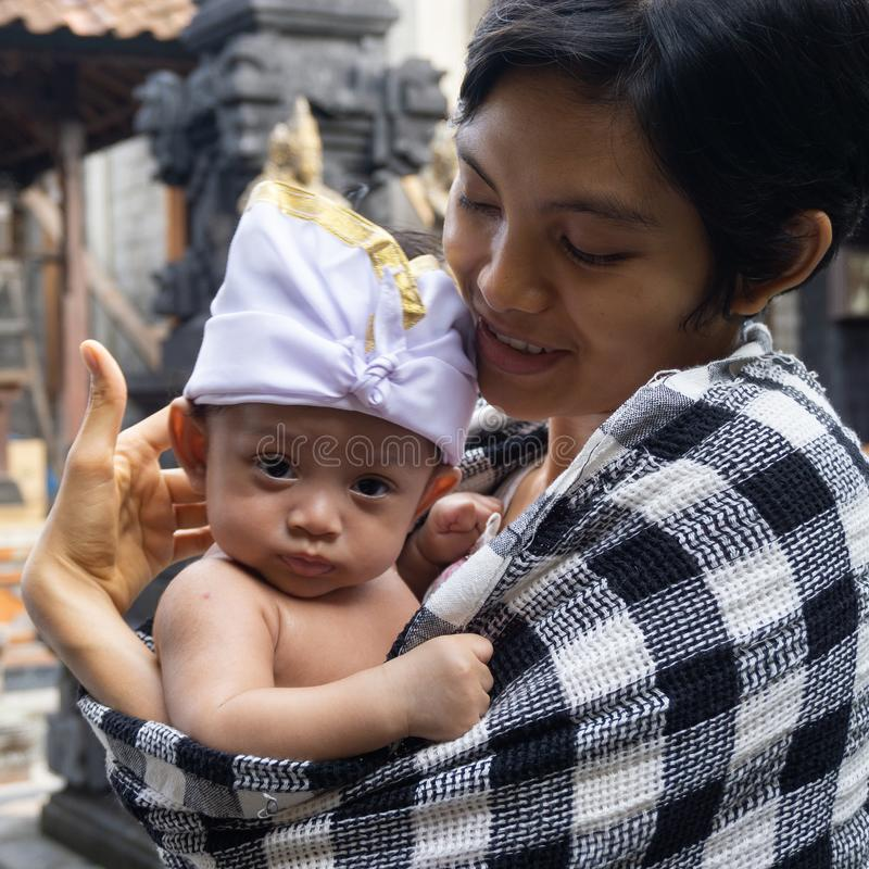 A portrait of a mother with her baby who is 3 months old in the mother`s arms. Babies pose using typical Balinese headbands and royalty free stock image