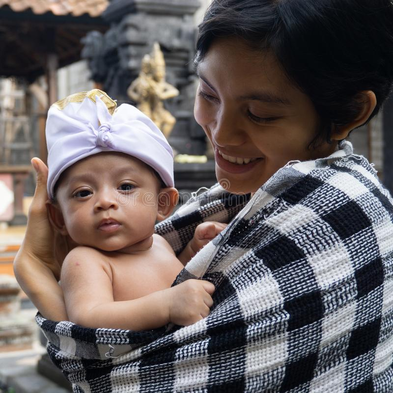 A portrait of a mother with her baby who is 3 months old in the mother`s arms. Babies pose using typical Balinese headbands and stock photo