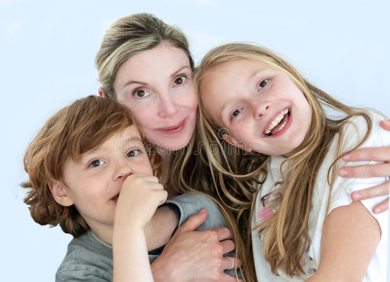 Portrait of a mother, with her children son 6 and daughter 11 in a jolly casual mood. The background is solid light blue. Portrait of a mother, with her children royalty free stock image
