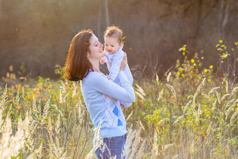 Portrait of mother with her new born baby in sunny park royalty free stock image