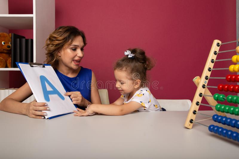Portrait of mother and kid together in a preschool studying. Portrait of mother and kid together in a preschool studying royalty free stock photos