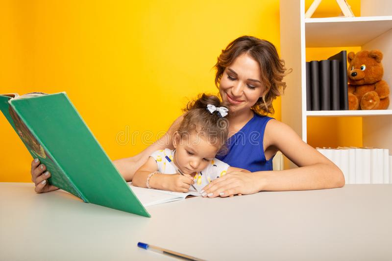 Portrait of mother and kid together in a preschool studying. Portrait of mother and kid together in a preschool studying royalty free stock photography