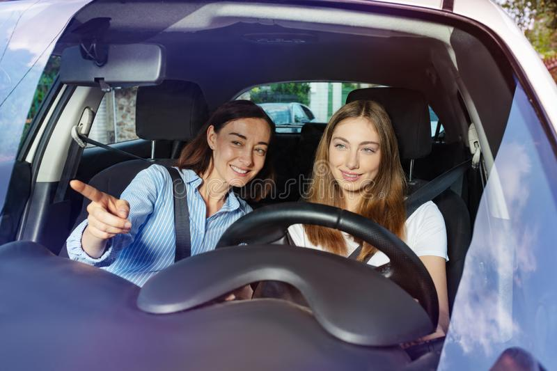 Teenage girl learning to drive with her mother stock images