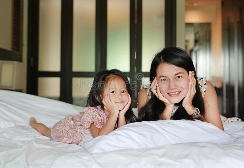 Portrait of mother and little asian girl looking camera and lying on bed at the morning royalty free stock photos