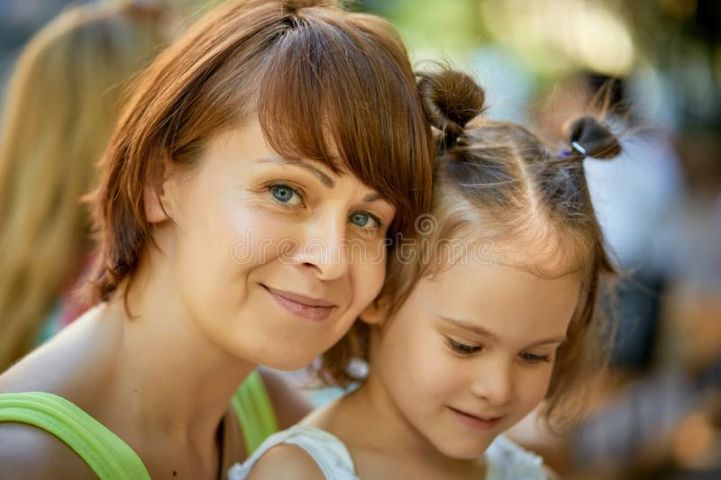 Portrait of mother and lovely little daughter at family picnic on summer day. royalty free stock photo