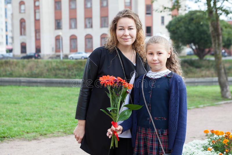 Portrait of mother and schoolgirl going back to school, daughter holding flower stock image