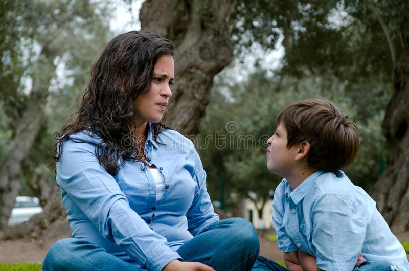 Portrait of a mother scolding to her son sitting on the grass stock photography