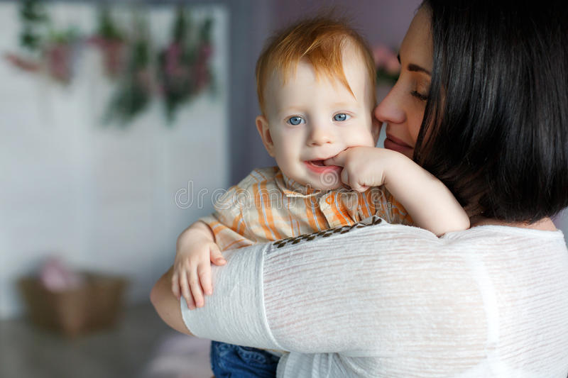 Portrait of a mother with a small red-haired son in her arms. Happy young mother,a women with black hair,red nail Polish,light makeup,dressed in a white blouse royalty free stock photos