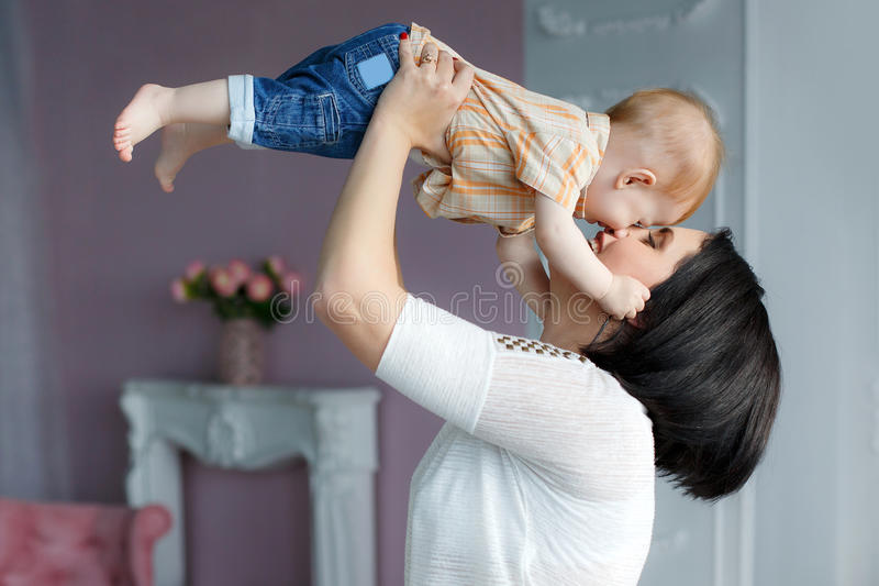 Portrait of a mother with a small red-haired son in her arms. Happy young mother,a women with black hair,red nail Polish,light makeup,dressed in a white blouse stock photography