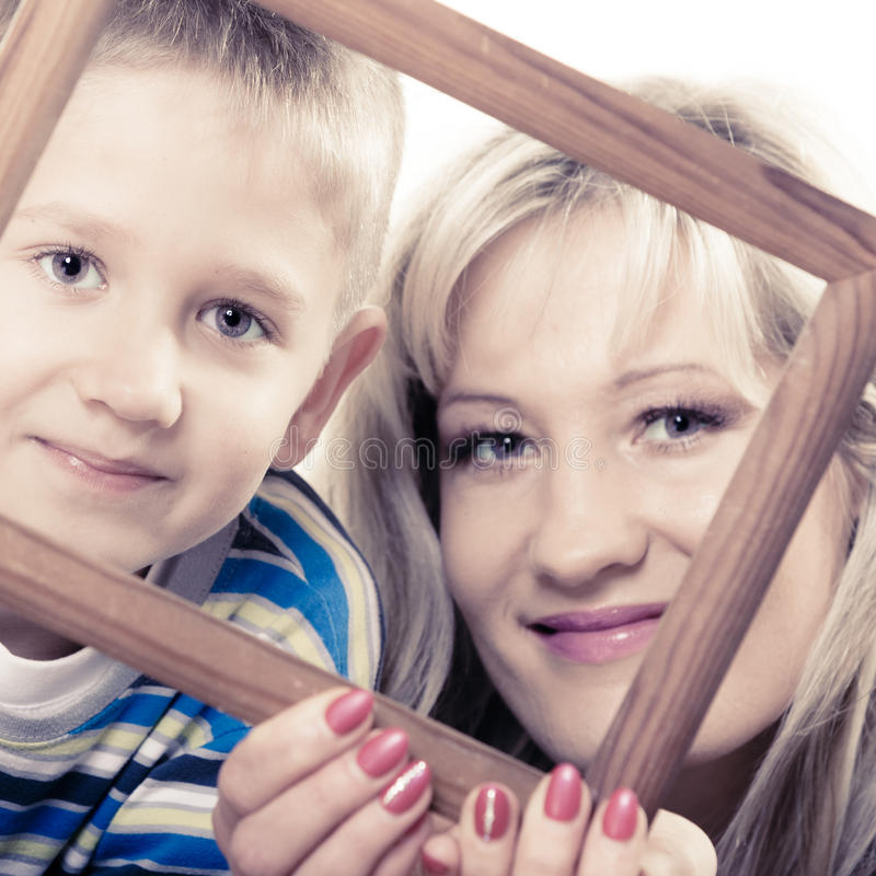 Portrait of mother and son holding photo frame royalty free stock photos