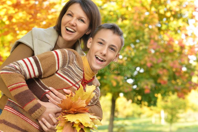 Portrait of a mother with son hugging outoors in autumnal park stock photos