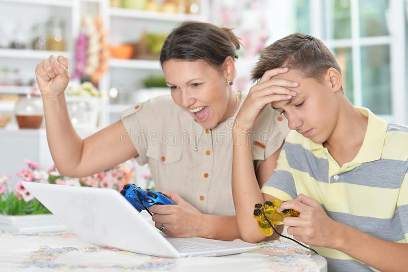 Portrait of mother and son playing computer game stock photography