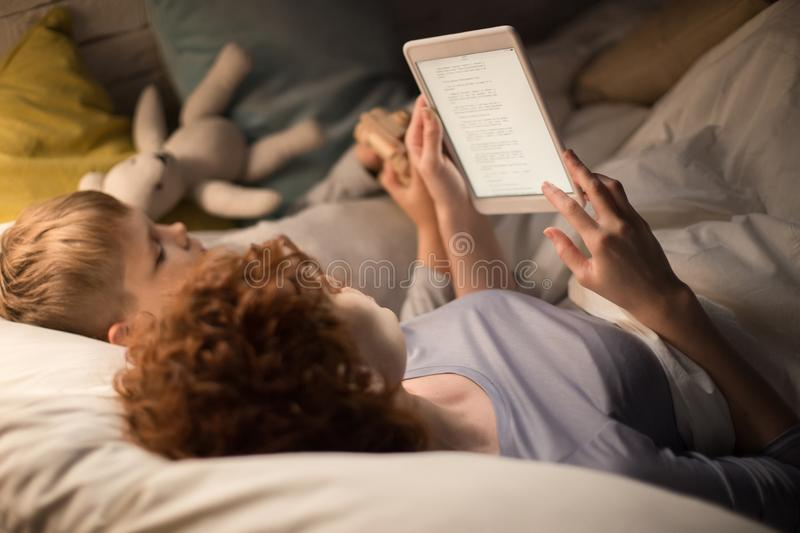 Mother and Son Reading Fairytales in Bed. Portrait of mother and son reading book together from tablet lying in bed before sleep, enjoying stories in dim royalty free stock photos