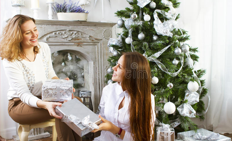 Portrait of a mother with teen daughter at home near the Christmas tree. Being happy and joyful royalty free stock photography