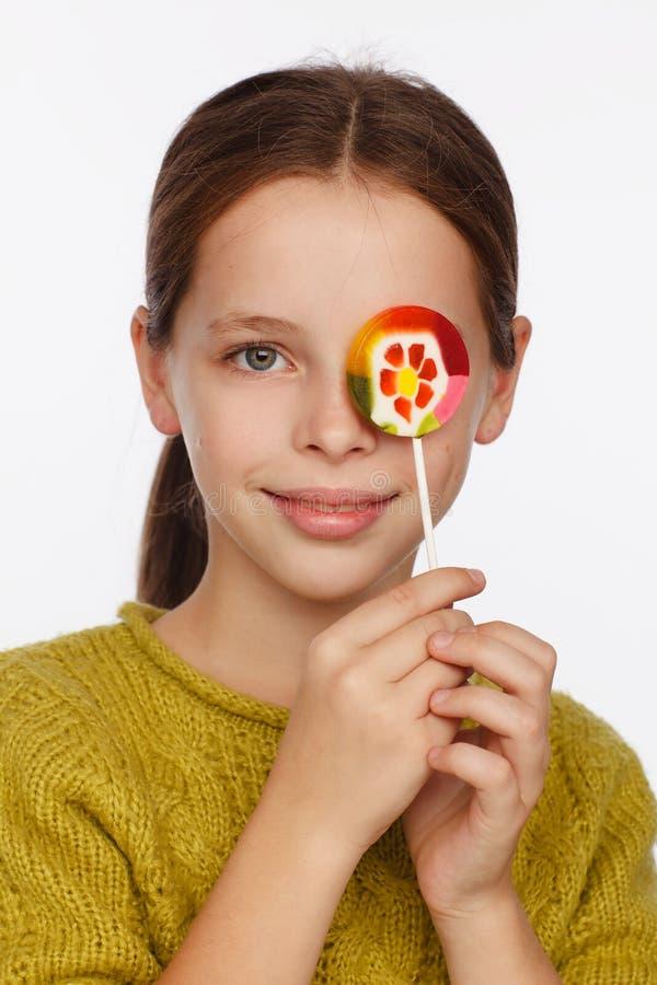 Portrait ?motif d'une fille de huit ans dans un chandail vert jaun?tre et avec une lucette dans des ses mains photos stock