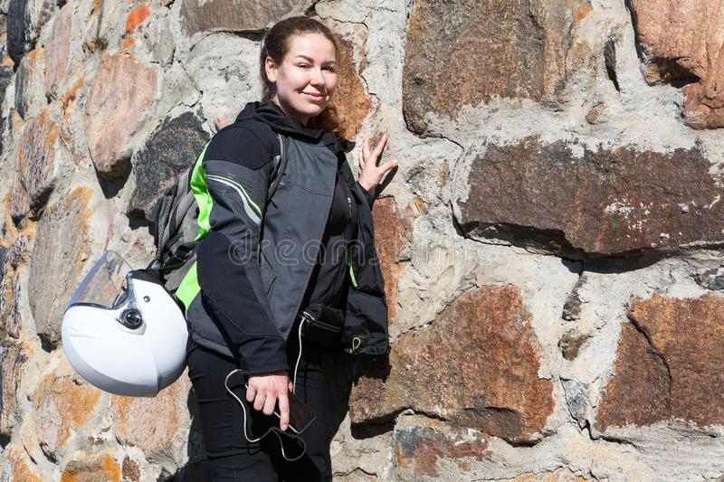 Portrait of motorcyclist woman stands near stone wall in apparel, with backpack on her back and helmet attached to it royalty free stock photo