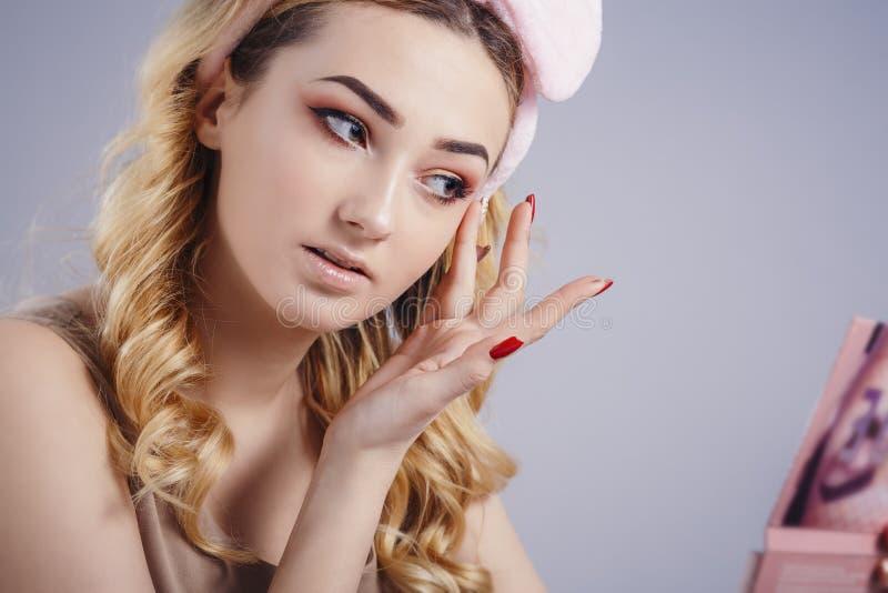 Portrait mou de studio d'une belle jeune femme avec le cercle mou pelucheux sur la tête faisant le maquillage devant un miroir da photo libre de droits