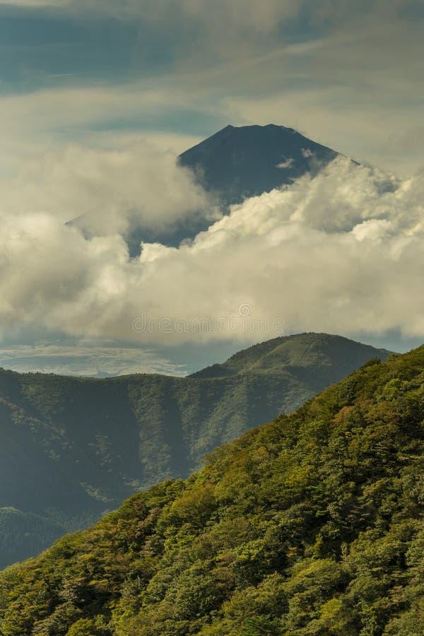 Portrait of mount Fuji summit peeking through clouds. stock photos