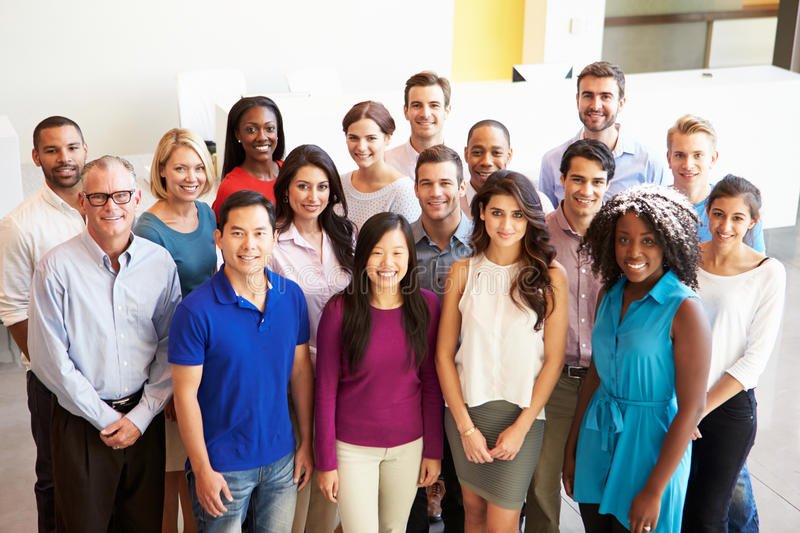 Portrait Of Multi-Cultural Office Staff Standing In Lobby. Smiling To Camera stock photography