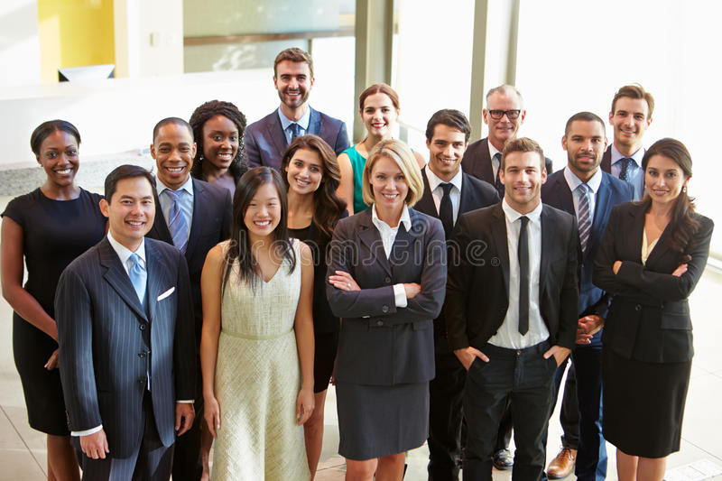 Portrait Of Multi-Cultural Office Staff Standing In Lobby. Wearing Smart Clothing Smiling stock photography