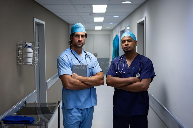 Male surgeons standing at hospital corridor stock photos