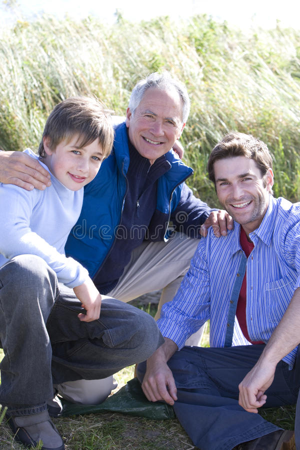 Portrait of multi-generation family crouching on beach royalty free stock photography