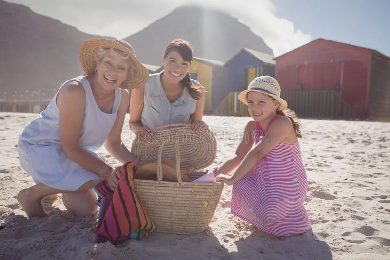 Portrait of multi-generation family by picnic basket at beach. Portrait of multi-generation family by picnic basket on sand at beach during sunny day royalty free stock images