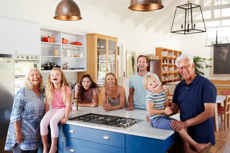 Portrait Of Multi Generation Family Standing Around Kitchen Island Together stock image