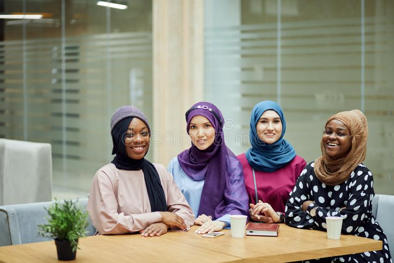 Multiracial group of muslim women dressed in national clothes posing in group stock images