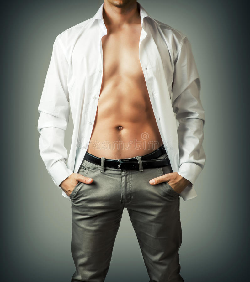 Portrait of muscle man torso in white shirt. On grey background royalty free stock image