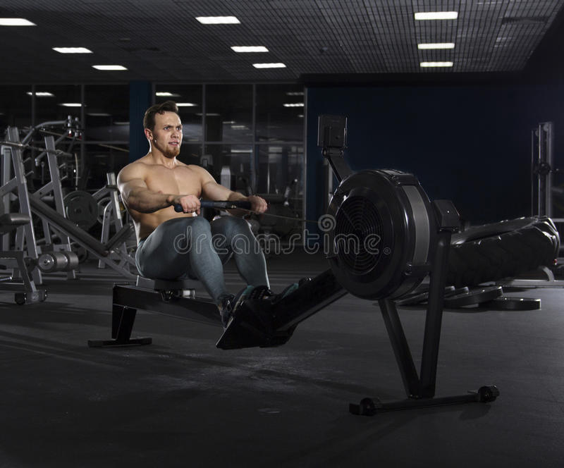 Portrait of muscular athlete working on rowing machine in modern stock photography