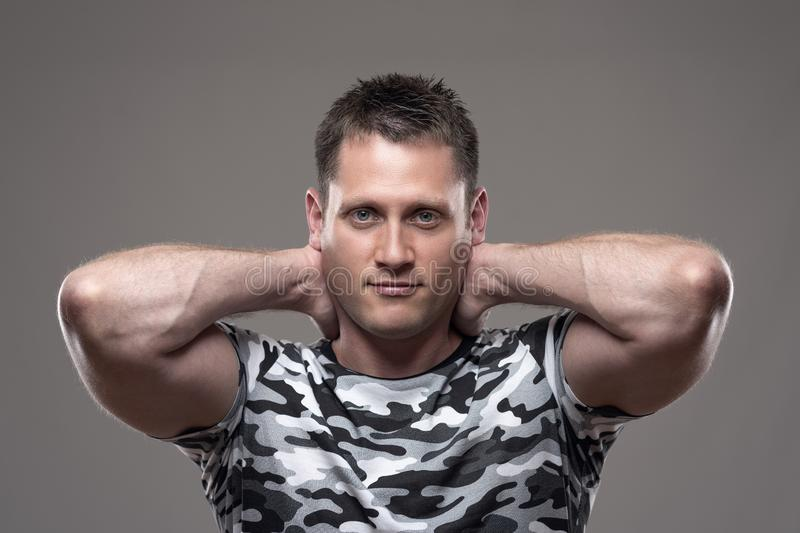 Portrait of muscular athletic young adult man in army shirt posing with hands behind head. Looking at camera royalty free stock images