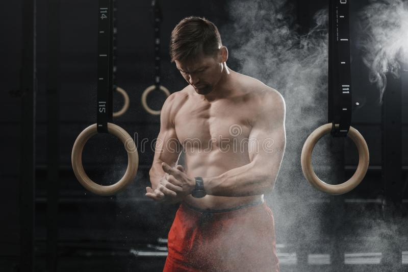 Portrait of muscular crossfit athlete clapping hands and preparing for workout at the gym. Cloud of dust chalk powder on dark background. Copy space stock photography