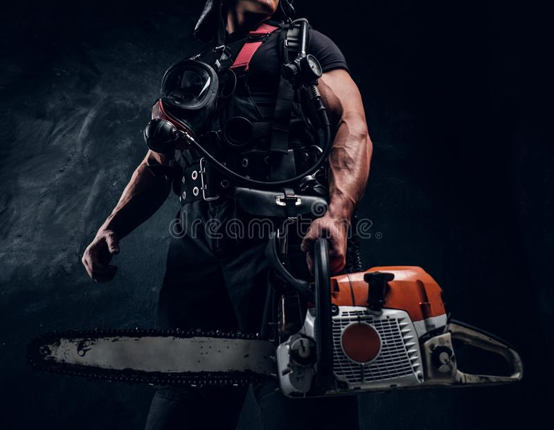 Portrait of muscular man with chainsaw and respirator royalty free stock image