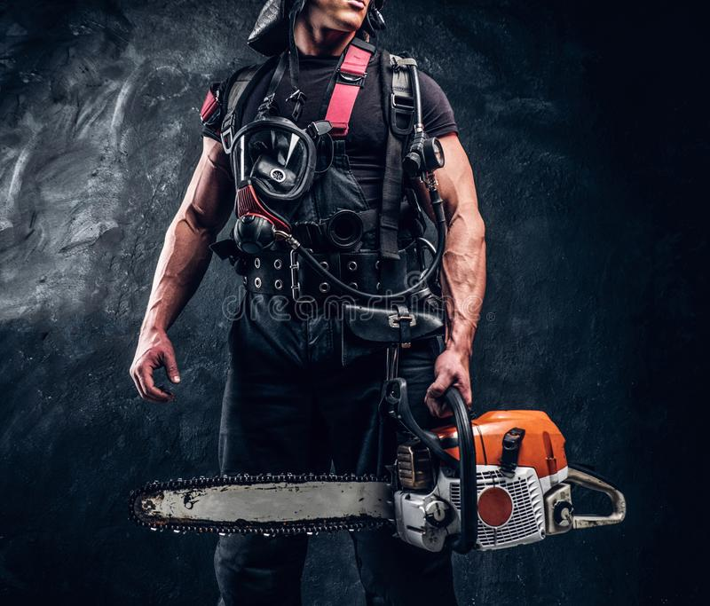 Portrait of muscular man with chainsaw and respirator stock photography