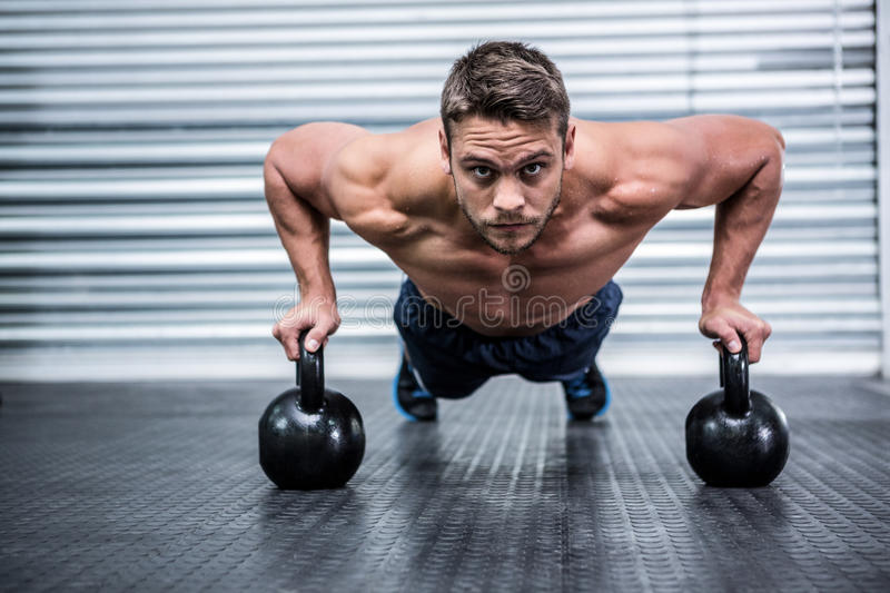 Portrait of muscular man doing push-ups with kettlebells stock image