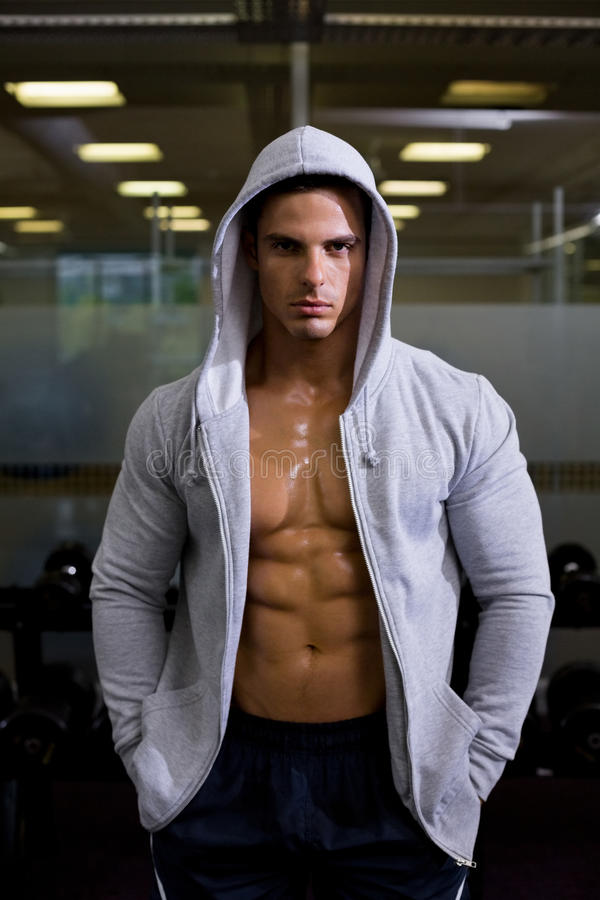 Portrait of a muscular man in hood jacket at gym royalty free stock photo