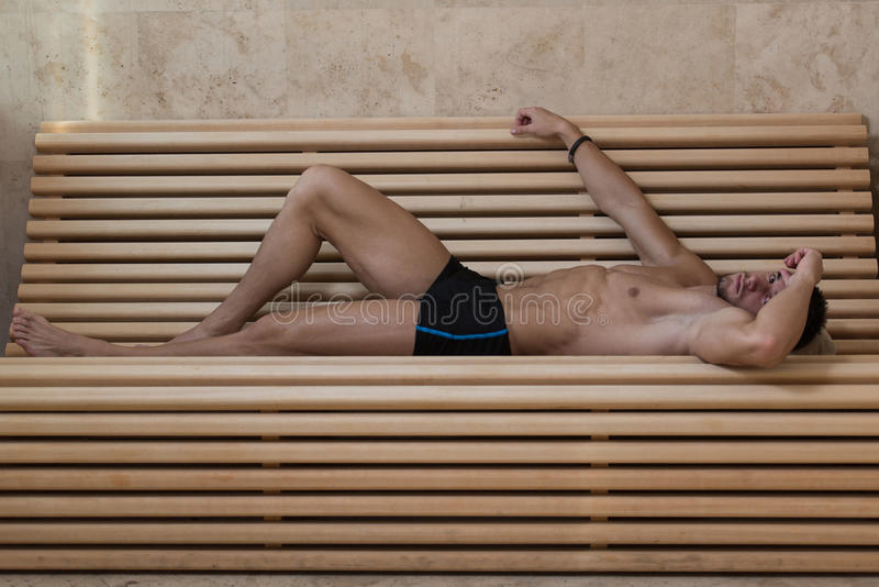 Portrait Of A Muscular Man Relaxing In Sauna. Happy Good Looking And Attractive Young Man With Muscular Body Relaxing In Sauna Hot royalty free stock image