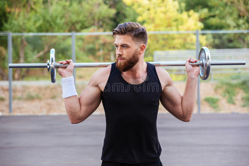 Portrait of a muscular man workout with barbell royalty free stock image