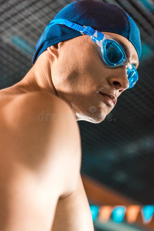 Swimmer. Portrait of muscular swimmer in swimming cap and goggles standing at swimming pool stock photo