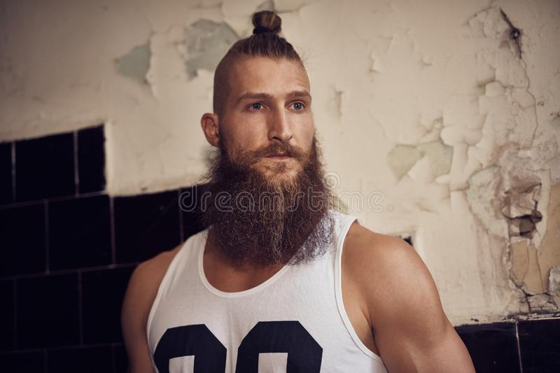 Muscular young bearded man in staircase stock photography
