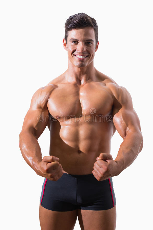 Portrait of a muscular young man clenching fists royalty free stock image