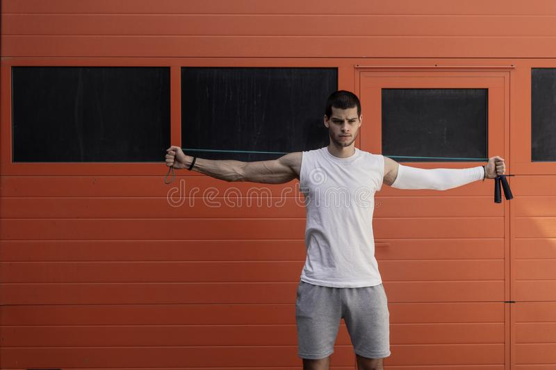 Portrait of muscular young man exercising, stretching with jumping rope stock photos