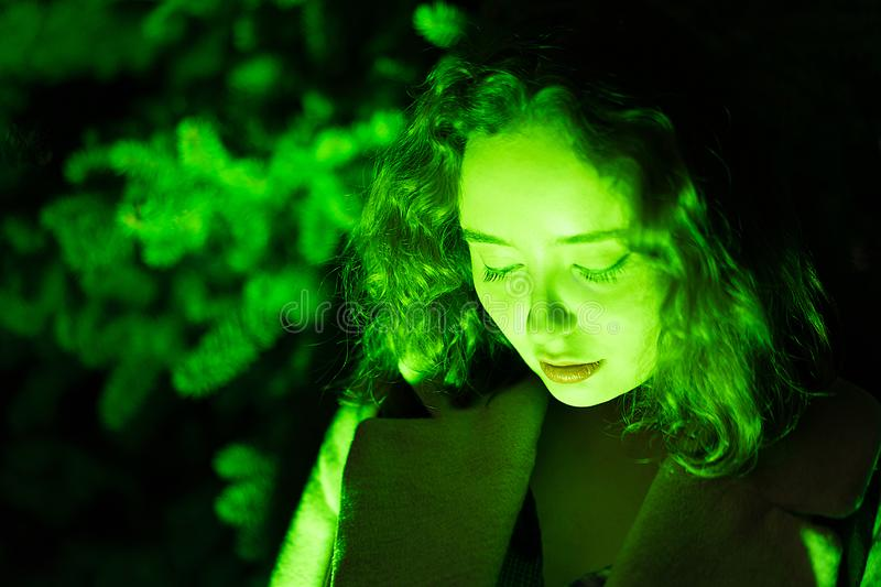 Portrait of a mysterious beautiful woman in green lighting with green background stock images