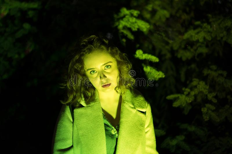 Portrait of a mysterious beautiful woman in green lighting. royalty free stock photo