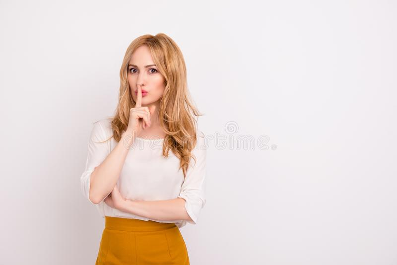 Portrait of mysterious businesswoman gesturing `shh!` against white background isolated on white background copy-space whisper s stock photo