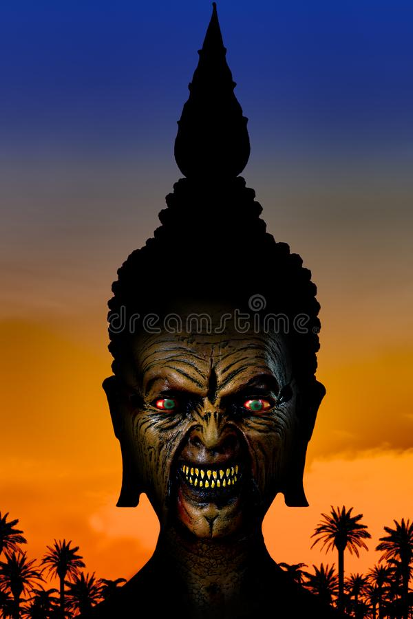 The portrait of mysterious creature. The spooky face with terrible grimace in helmet. The portrait of mysterious creature on color background with sunset and stock image