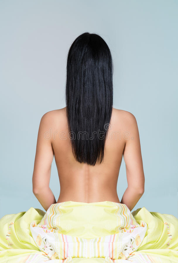 Woman with long black hair sitting on the bed royalty free stock images