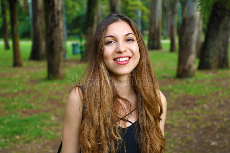 Portrait of natural young woman in the park with trees on the background stock image