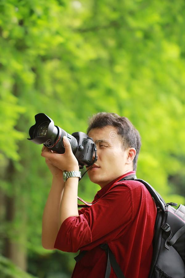 Portrait of a nature photographer cover his camera screen with face in a spring park garden forest stock image
